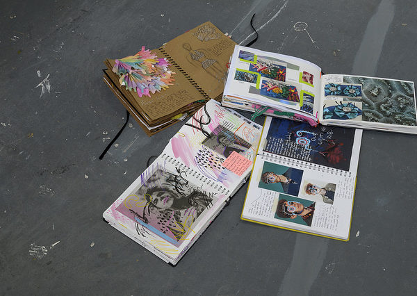 Foundation Diploma in Art & Design student notebooks arrayed on concrete floor